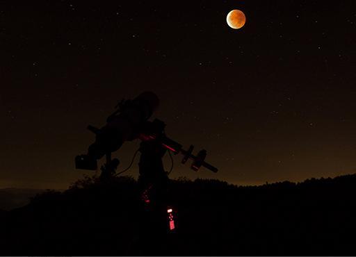 Totale Mondfinsternis mit Aufnahmegerät im Vordergrund und verfinstertem Mond im Hintergrund, aufgenommen im Schwarzwald 2015 (Foto: Marcel Süssli).